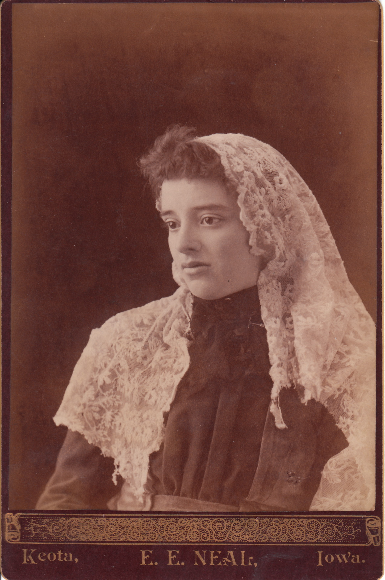 The woman is wearing a large lace veil or kerchief