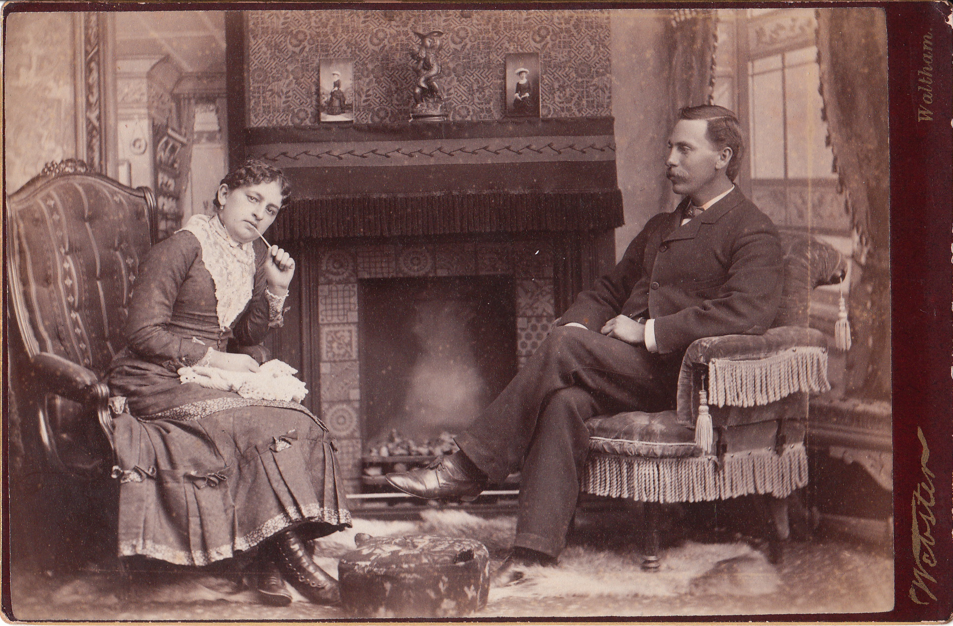 Couple Sits In Front Of A Fireplace In Comfortable Living