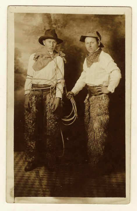 This vintage real photo postcard captures two cowboys in an interesting  scene. One of the cow pokes is tied up as if he's a criminal.